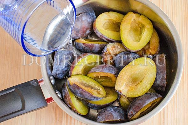 Выкладываем половинки слив в кастрюлю, добавляем воду