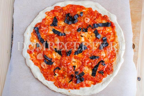 Смазываем пиццу соусом, посыпаем базиликом