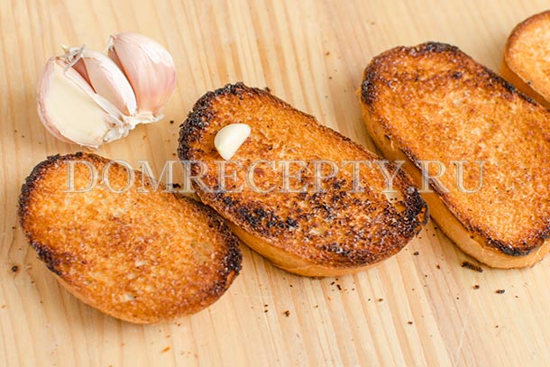 Натираем ломтики хлеба чесноком