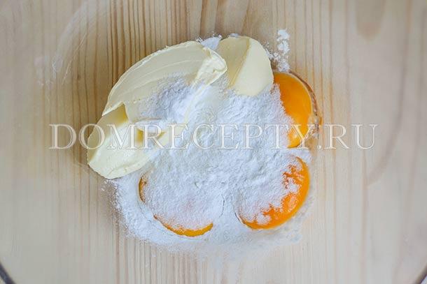 Добавляем к желткам крахмал, сливки и половину сахарной пудры