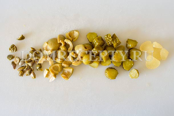 Измельчаем оливки, каперсы, чеснок и корнишоны