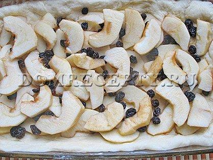 Укладываем на тесто нарезанные яблоки и изюм