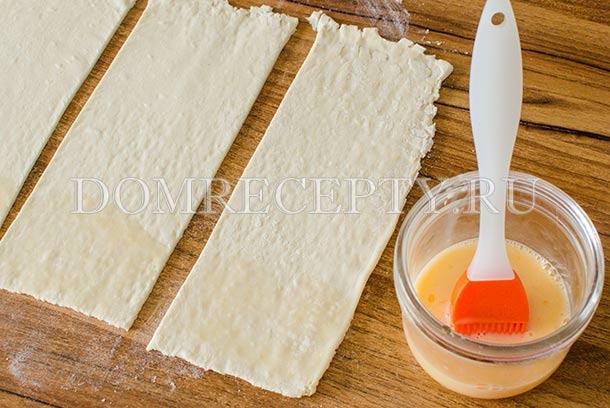Нарезаем тесто на полоски, смазываем взбитым яйцом