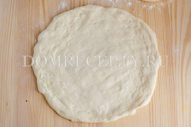 Руками расплющиваем тесто в лепешку