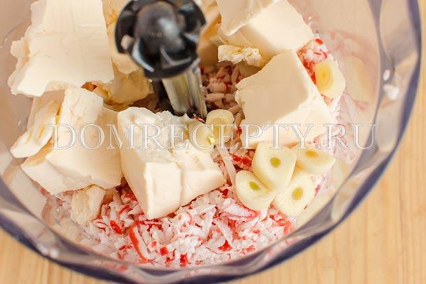 Отправляем в блендер треть крабовых палочек, плавленный сыр и чеснок